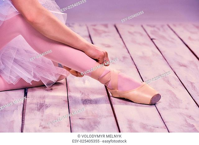 Professional ballerina putting on her ballet shoes on the wooden floor on a pink background. feet close-up