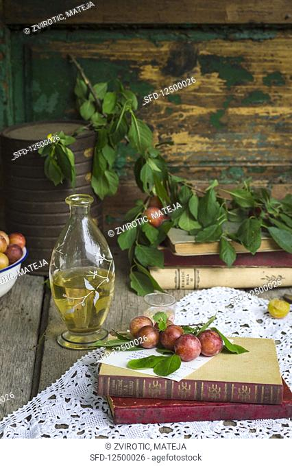 Fresh mirabelle plums in rustic enviroment with bottle of rakija (fruit brandy)