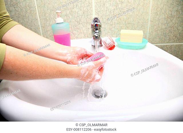 Woman wash soapy hands in bathroom