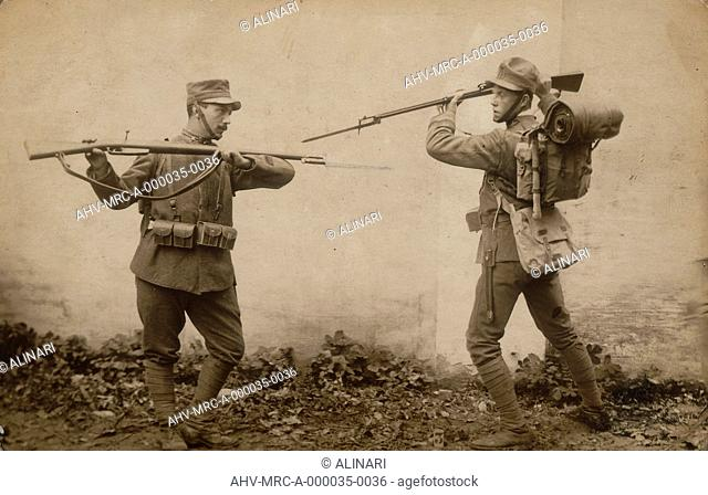Album R. Esercito I G. M. (Prima Guerra Mondiale): sergeant in uniform with rifle and bayonet in war training with a soldier loaded backpack, shot 10/1915