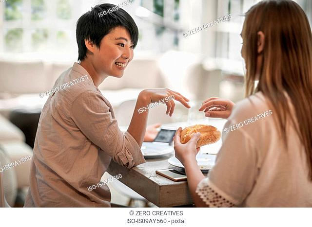 Women chatting over drinks and snacks