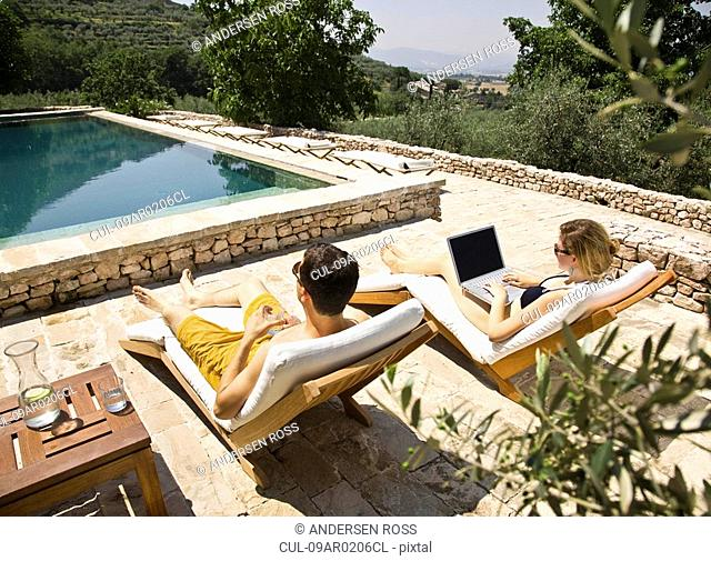 Woman working on computer by the pool