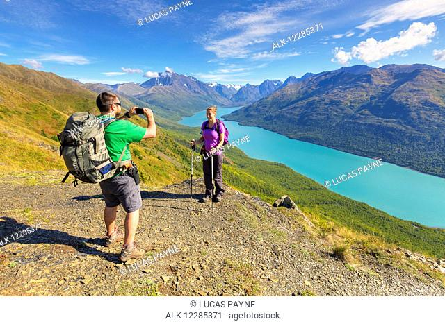 Hikers taking pictures along the Twin Peaks Trail, Eklutna Lake, Chugach State Park, Southcentral Alaska, Summer
