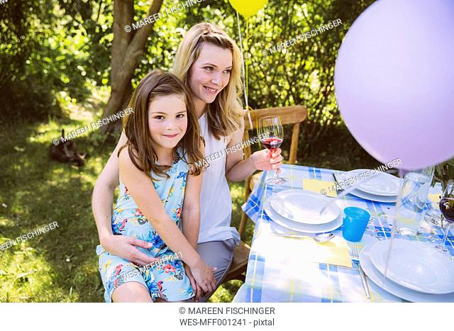 Daughter sitting on mother's lap at garden party table
