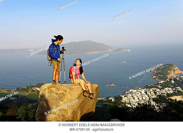 Hikers on rock, Dragons Back Trail, view on Shek O Bay, Hong Kong, China