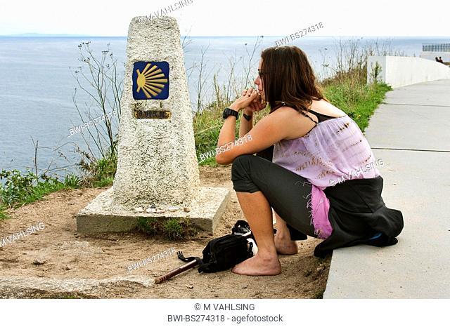 young woman at kilometre stone zero reflecting her pilgrimage, Spain, Galicien, Provinz A Coruña, A Corua, Kap Finisterre, kelt. Fisterra