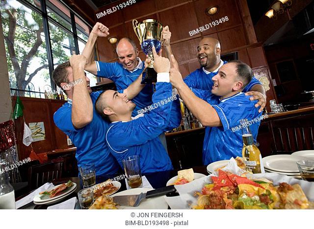 Cheering teammates and man lifting trophy