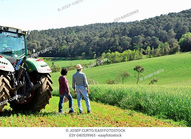 couple of farmers looking at a field. Porqueres, Girona province, Spain
