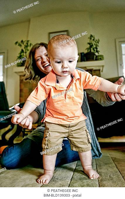 Caucasian mother helping baby walk on living room floor