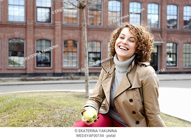 Portrait of happy woman with curly hair sitting on a meadow eating an apple