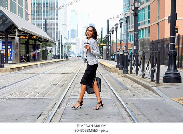 Businesswoman crossing light rail tracks