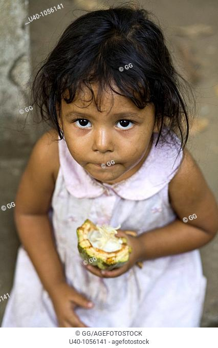 Guatemala, young girl eating fresh cacao