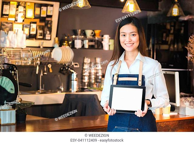 Smiling asian woman barista holding blank tablet compute in front of coffee shop counter bar,Mock up space for display of menu or design,clipping path on screen
