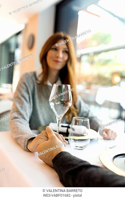Woman holding hands with man in a restaurant