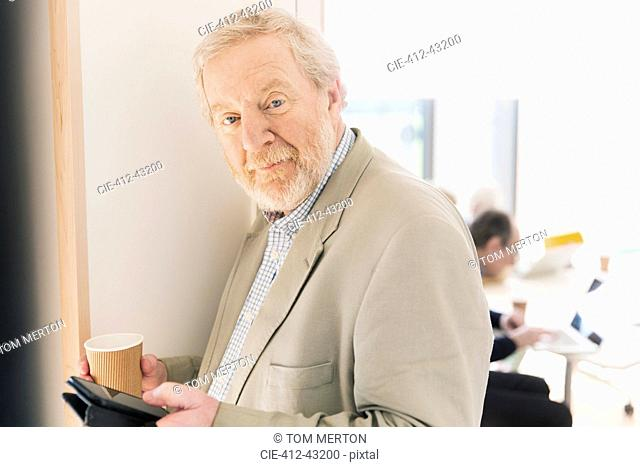 Portrait confident senior businessman with digital tablet