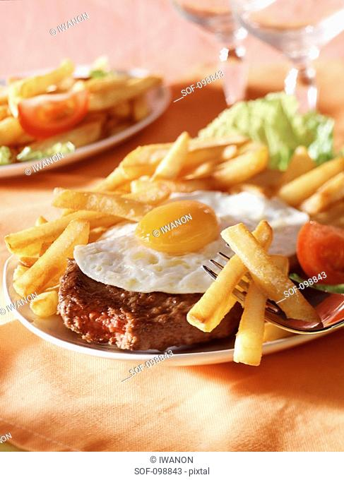 Hamburger with a fried egg on top and chips