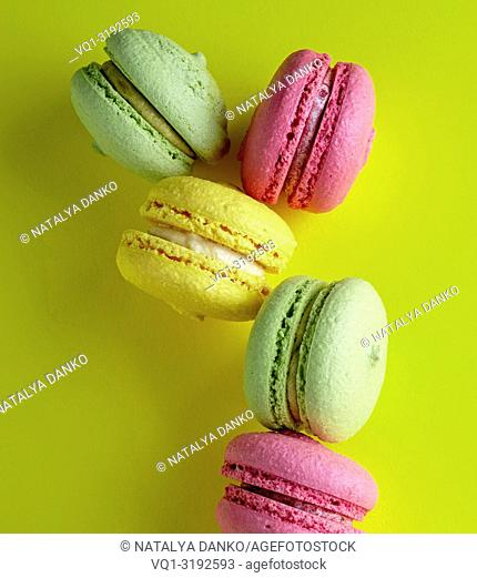 multicolored round almond meal meringue pastries macarons on a bright yellow background, close up