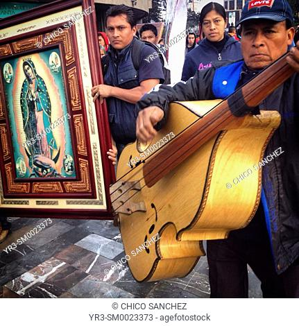 A pilgrim plays the bass guitar as others carry images of Our Lady of Guadlaupe during the annual pilgrimage to the Our Lady of Guadalupe basilica in Mexico...