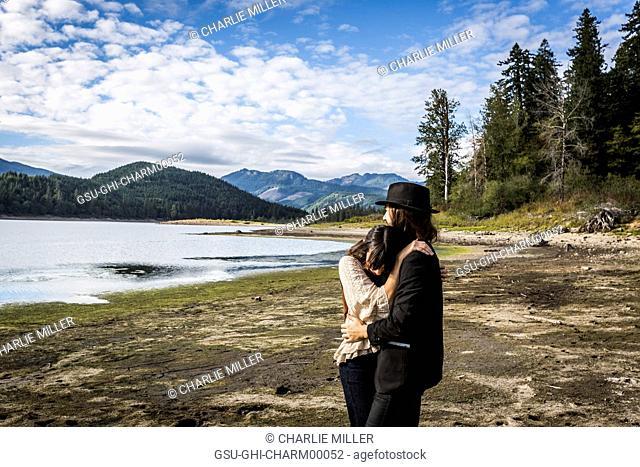 Bohemian Couple Embracing with Scenic Landscape in Background, Merrill Lake, Washington, USA