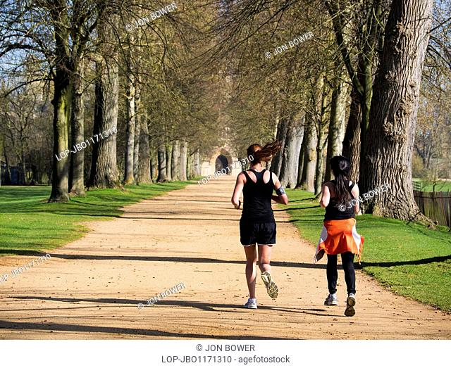 England, Oxfordshire, Oxford. Two students jogging in Christ Church Meadows in Oxford