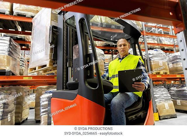 loader with clipboard in forklift at warehouse
