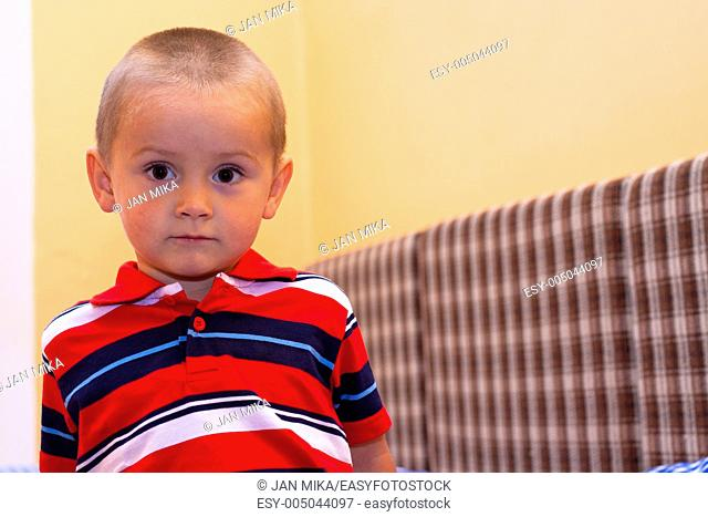 Portrait of little boy sitting on the bed