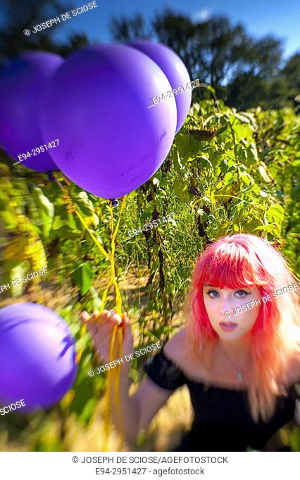 A 25 year old woman with pink hair, looking at the camera in a field of sunflowers holding balloons, Alabama USA