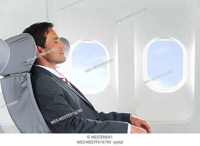 Germany, Bavaria, Munich, Mid adult businessman relaxing in business class airplane cabin