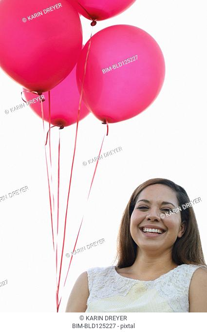 Mixed race woman with pink balloons