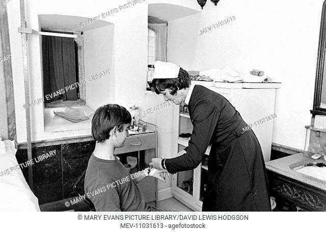 Nurse bandaging an injured schoolboy's hand in the sick bay at Atlantic College (United World College of the Atlantic), St Donat's Castle, Llantwit Major