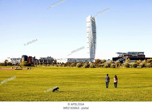 Rear view of couple walking at park with Turning Torso skyscraper in background