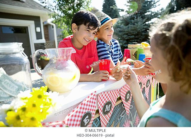Girl buying lemonade from boys at lemonade stand in sunny driveway