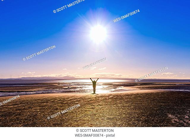 Great Britain, Scotland, Solway Firth, silhouette of female tourist, raised arms