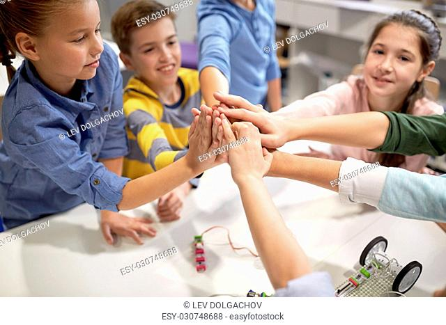 education, children, technology, science and people concept - group of happy kids building robots and making high five gesture at robotics school
