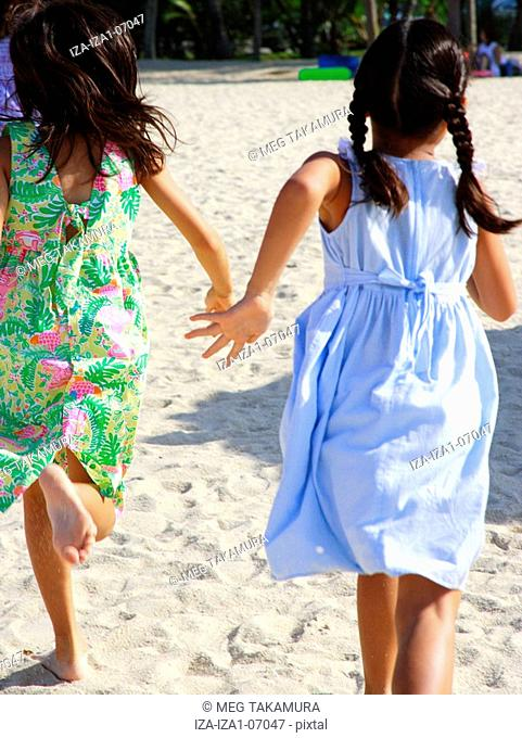 Rear view of two girls running on the beach