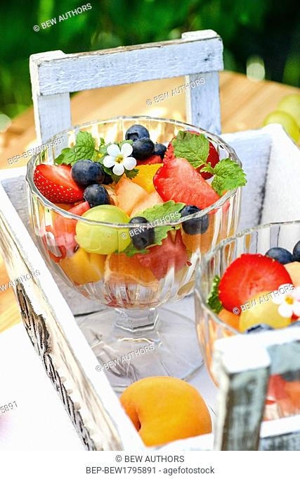 Fresh fruit salad in a glass dish in the garden. Selective focus