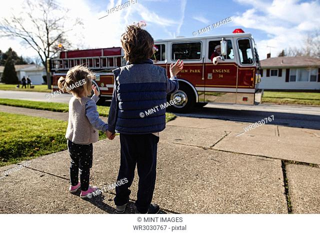 Rear view of young boy and girl standing on a pavement, holding hands, watching fire engine driving past on street