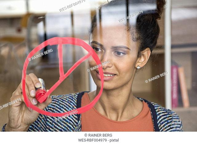 Woman drawing symbol on glass pane in office