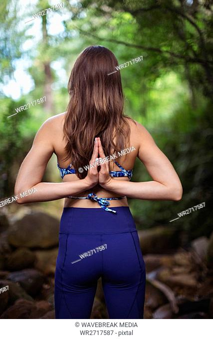 Rear view of woman performing yoga in forest