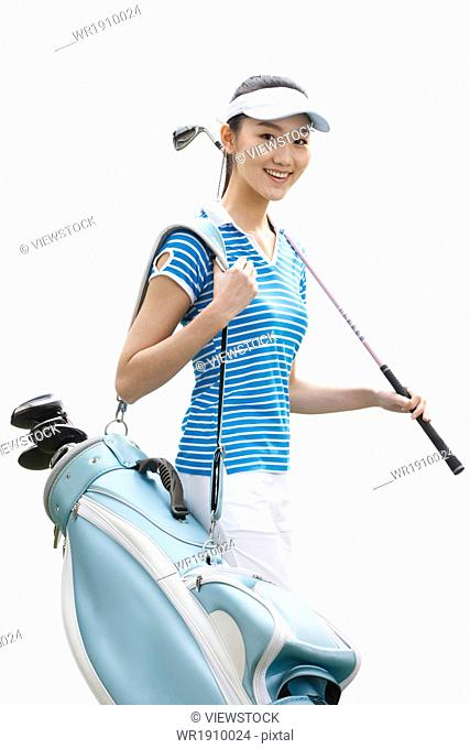 A young woman carrying a golf bag