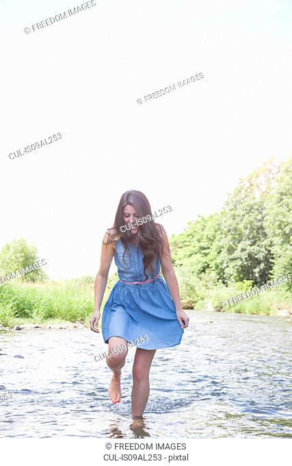 Young woman in shallow stream