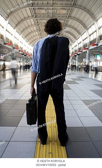 Rear view of businessman holding briefcase