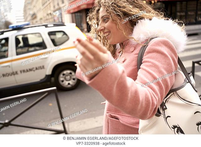 woman moving arms at street in city, in Paris, France