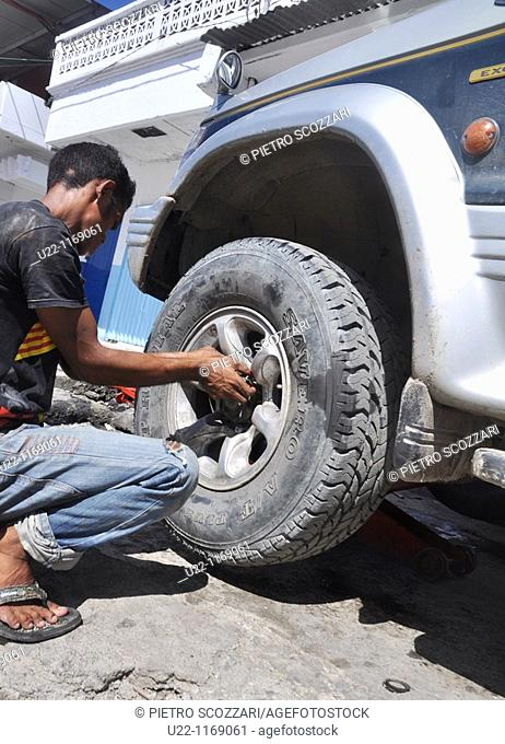 Dili (East Timor): a man changing a wheel in the street