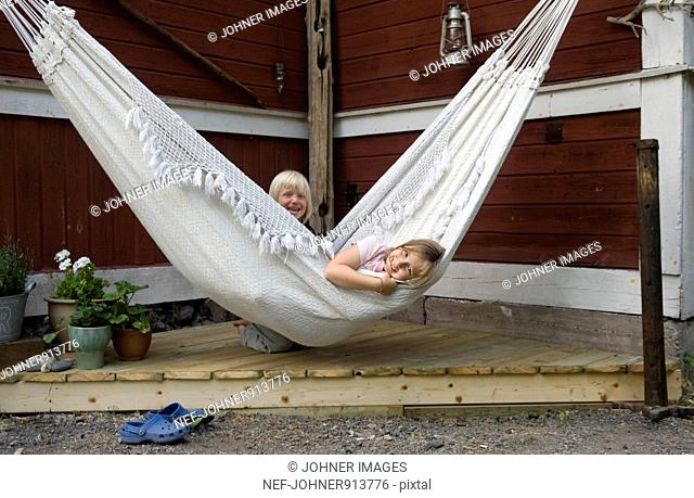 Girl relaxing in hammock, boy in background