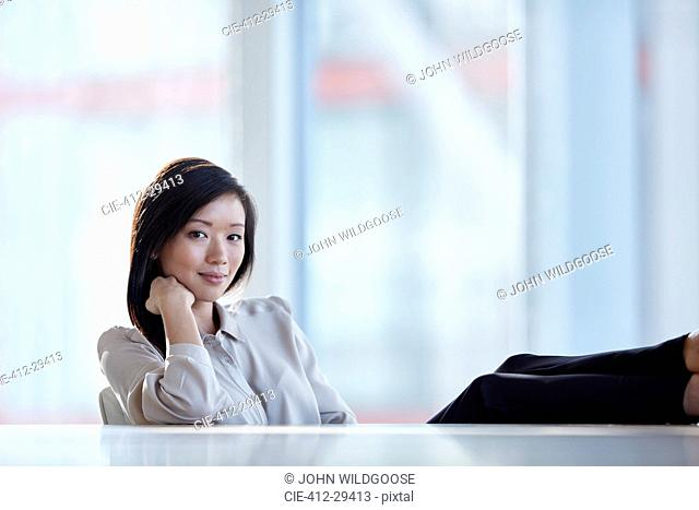 Portrait confident businesswoman with feet up