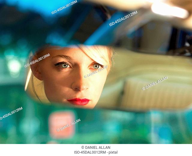 Woman reflected in rearview mirror