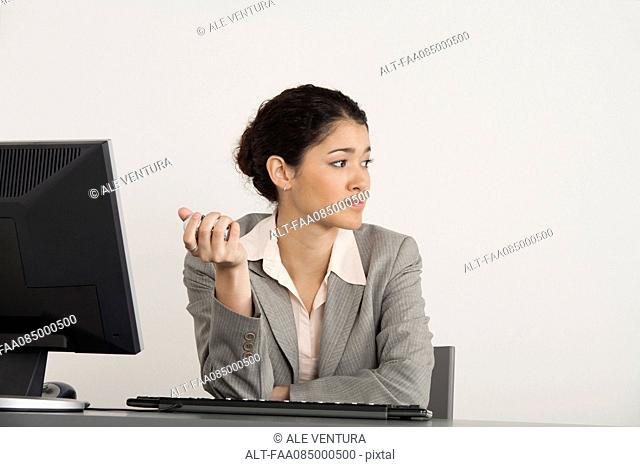 Young businesswoman holding yin g balls at desk