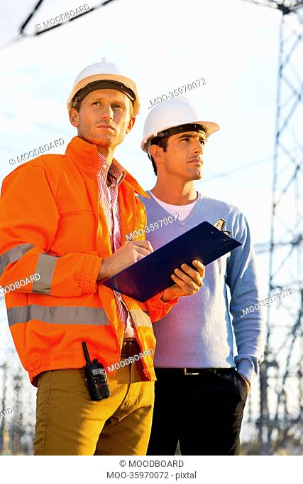 Male architects with clipboard inspecting site together