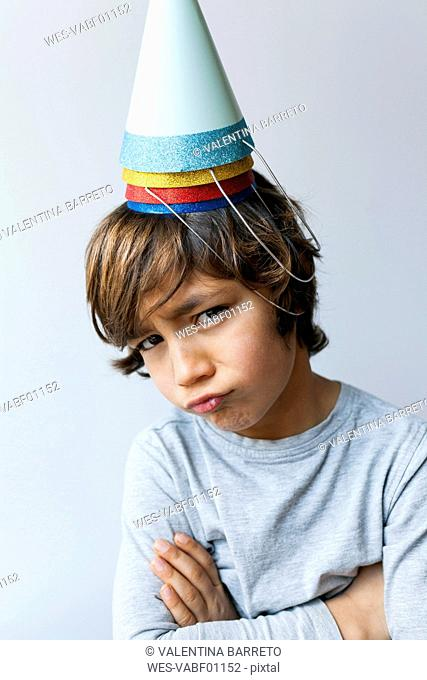 Portrait of little boy with four party hats on his head pouting mouth